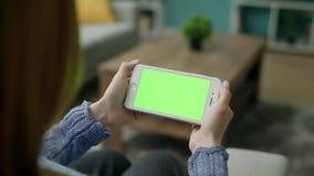 Mujer en casa que localiza en un sof? usando con la pantalla verde Smartphone de la maqueta metrajes
