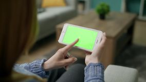 Mujer en casa que localiza en un sof? usando con la pantalla verde Smartphone de la maqueta almacen de metraje de vídeo