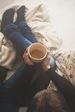 Mujer en casa que se sienta en la butaca cómoda y el té de consumición, visión desde arriba Foto de archivo libre de regalías