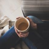 Mujer en casa que se sienta en la butaca cómoda y el té de consumición, visión desde arriba Imagen de archivo libre de regalías