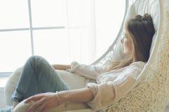 Mujer en casa que se sienta en silla moderna delante de la ventana que se relaja en su sala de estar Fotografía de archivo