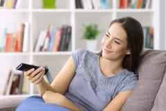 Mujer en casa que ve la TV el considerarse teledirigida Imágenes de archivo libres de regalías