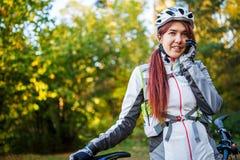 Mujer en casco de la bicicleta que habla en el teléfono en bosque del otoño Fotografía de archivo