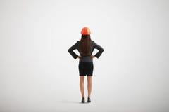 Mujer en casco del desgaste formal y de la construcción con su akimb de los brazos Imágenes de archivo libres de regalías