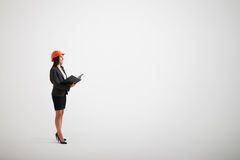 Mujer en casco del desgaste formal y de la construcción con una carpeta Fotos de archivo libres de regalías