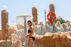 Mujer en centro turístico tunecino del aquapark debajo de la ducha foto de archivo libre de regalías