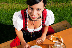 Mujer en cerveza de consumición del Dirndl Imagen de archivo libre de regalías
