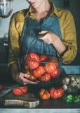 Mujer en cesta de la tenencia del delantal con los tomates de la herencia imagen de archivo libre de regalías