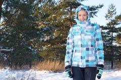 Mujer en chaqueta azul que camina en bosque del invierno Fotografía de archivo libre de regalías