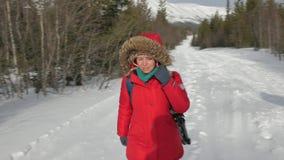 Mujer en chaqueta caliente con los paseos turísticos de la mochila en el camino almacen de video