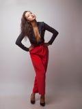 Mujer en chaqueta de las rayas y pantalones rojos Imagenes de archivo
