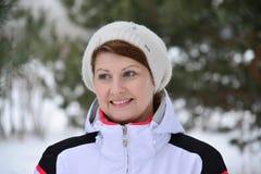 Mujer en chaqueta y sombrero de deportes en el bosque del pino del invierno Fotos de archivo libres de regalías