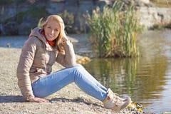 Mujer en chaqueta y vaqueros que se sientan cerca del lago Fotografía de archivo