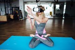 Mujer en clase de la yoga con las auriculares de VR Imagen de archivo libre de regalías