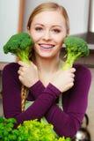 Mujer en cocina con bróculi fresco verde Foto de archivo