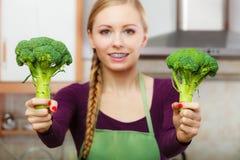 Mujer en cocina con bróculi fresco verde Fotos de archivo