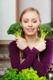 Mujer en cocina con bróculi fresco verde Imágenes de archivo libres de regalías