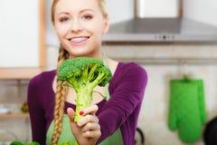 Mujer en cocina con bróculi fresco verde Imagenes de archivo