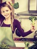 Mujer en cocina con bróculi fresco verde Fotos de archivo libres de regalías