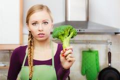 Mujer en cocina con bróculi fresco verde Fotografía de archivo
