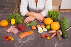 Mujer en cocina con diversas comidas crudas Fotos de archivo libres de regalías
