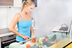 Mujer en cocina con la computadora portátil Foto de archivo