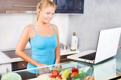 Mujer en cocina con la computadora portátil Imagenes de archivo