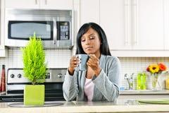 Mujer en cocina con la taza de café Fotografía de archivo libre de regalías