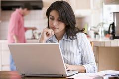 Mujer en cocina con papeleo usando la computadora portátil Foto de archivo libre de regalías