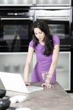 Mujer en cocina elegante Fotografía de archivo libre de regalías