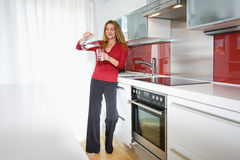 Mujer en cocina moderna imagen de archivo
