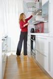 Mujer en cocina moderna fotografía de archivo libre de regalías