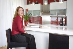 Mujer en cocina moderna imagen de archivo libre de regalías
