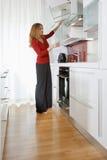 Mujer en cocina moderna fotos de archivo