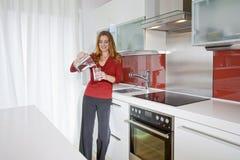 Mujer en cocina moderna imagenes de archivo