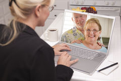 Mujer en cocina usando el ordenador portátil - en línea con los pares mayores Imagenes de archivo