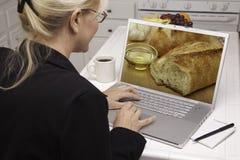 Mujer en cocina usando la computadora portátil - alimento y recetas Fotografía de archivo libre de regalías