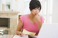 Mujer en comedor con el pensamiento de la computadora portátil fotografía de archivo libre de regalías