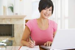 Mujer en comedor con la sonrisa de la computadora portátil Foto de archivo