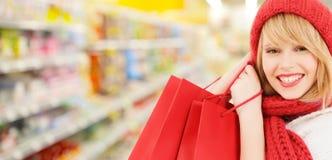Mujer en compras del sombrero y de la bufanda en el supermercado Fotografía de archivo