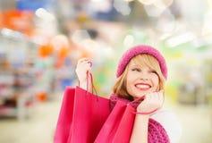 Mujer en compras del sombrero y de la bufanda en el supermercado Imagen de archivo libre de regalías