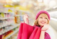Mujer en compras del sombrero y de la bufanda en el supermercado Fotografía de archivo libre de regalías