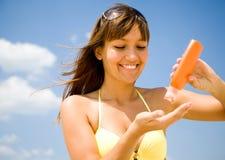 Mujer en crema protectora de la mancha del bikini Fotografía de archivo