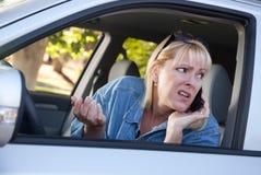Mujer en cuestión que usa el teléfono celular mientras que conduce Fotos de archivo libres de regalías