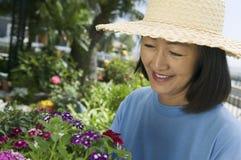 Mujer en cultivar un huerto del sombrero de paja Fotos de archivo libres de regalías