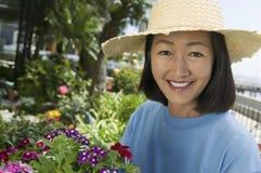 Mujer en cultivar un huerto del sombrero de paja Imágenes de archivo libres de regalías