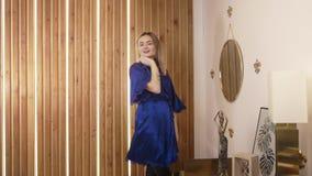 Mujer en danzas de la albornoz en su dormitorio cerca del espejo antes de hacer maquillaje, belleza y estilo en el maquillaje de  almacen de metraje de vídeo
