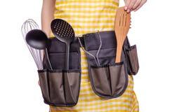 Mujer en delantal con las herramientas de la cocina imagenes de archivo
