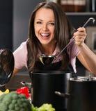 Mujer en delantal en cocina moderna Imagenes de archivo
