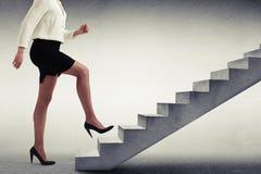 Mujer en desgaste formal que camina encima de las escaleras Imagenes de archivo